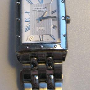 Et flot ur fra Raymond Weil - model Tango. 2 ekstra led medfølger + æske og købsbevis. Har bare ligget i skuffen de sidste år. Uret har lidt brugsspor som er svært helt at undgå. Skal have et nyt batteri. Materiale: Stållænke og urkasse Mål: Urkassens bredde 2,5 cm, længde 3 cm Oprindelig butikspris var 5150 kr. - købt med rabat for 4635 kr. BYD