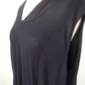 Tunika/kjole i viscose/elastan i assymetriske længder og med lommer og hætte.  Brugt et par gange med f.eks. t.shirt og matchende leggings. Let og luftig. Brystvidde 118, længde 90/105 Str. 3 = 46/48 Nypris 900 kr.