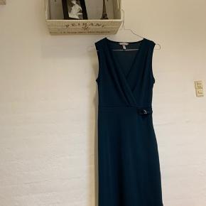 Mørkeblå/peteoloumsblå kjole, som ligner en slå om kjole, men som ikke skal bindes, da det blot er formen på kjolen. Den er brugt en gang og er egentlig en XS, men fitter en S/M.  Sælges, da jeg ikke selv får den brugt.  Skriv endelig for flere billeder og byd gerne.