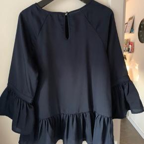 Mørkeblå tunika/top, med puf ærmer og skørt forneden. Knappe lukning på ryggen. Spørg for mere info/billeder og BYD gerne