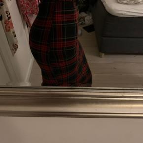 Stram knælang nederdel, meget taljeret, og kommer med bælte. Kun prøvet på. Nederdelen har en slids bagpå
