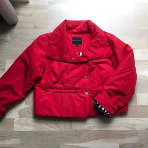 Let vatteret  kort jakke i postkasserød med stribet for. Længden er  50 cm.