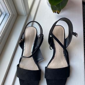 Sindssyg sød sandal med hæl, i ruskinds look!  Købt i Polen, men er for smal til min fod, derfor aldrig brugt.  Passer en str 39.