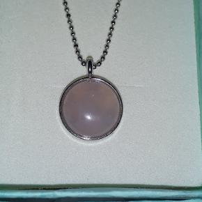 Eget design.  Halskæde i stål, 44 cm, vedhæng med lys rosa sten, måler 1.4 cm i diameter.  Halskæden leveres i gaveæsker og kan sendes for 10 kr med Post Nord, almenlig brev.