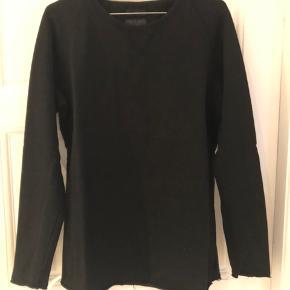 Sort langærmet T-shirt i kraftig bomuldskvalitet. Rå kanter i ærmer og bund. Brugt men pæn stand