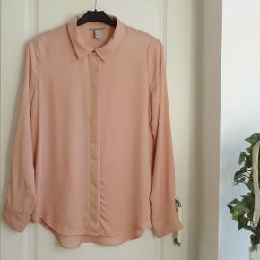 Skjorte, H&M, str. 36, Rosa, 100 % polyester, Ubrugt  Ny ubrugt  En super flot kvalitets skjorte i 100 % rosa polyester  Er rigtig dejlig let og behagelig at have på  Har skjulte knapper hele vejen ned i for  Sender gerne hvis køber betaler fragt 37 kr