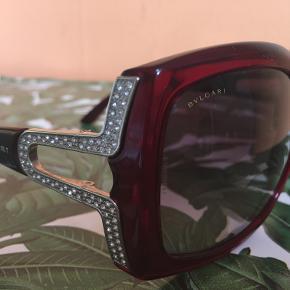 BULGARI DESIGNER SOLBRILLE.  Super klassiske og giver altid et stilfuldt look!  Købt i Harrods, London for nogle år tilbage. De er lavet med Swarovski krystaller på siderne - samt kan autentitets nummeret også ses for at bevise ægtheden.  Bulgari har også lavet en udgave af denne brille med ægte diamanter.  Der er nogle ridser i selve glasset men kan kun ses når man kommer helt tæt på. Det er ikke noget der bemærkes overhovedet når man har solbrillerne på.  Kan afhentes i Næstved / KBH hvis forsendelse ikke ønskes.