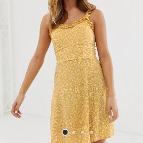 Off gul sommerkjole med hvis små blomst print, går til over knæene, elastik i ryggen, krøllede stropper, købt fra Asos og aldrig brugt. Prisen er ikke fast, byd endelig! :)