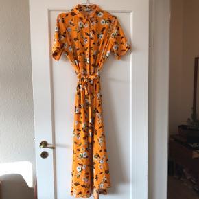 Flot blomstret kjole fra Envii i str. S men oversize fit 🍊 har knapper hele vejen ned. Maxikjole med hvide blomster i smuk orange farve 💃🏻 har bindebånd i taljen. Har fået en sort plamage nederst bagpå, se billede nr. 6.   Bemærk - afhentes ved Harald Jensens plads eller sendes med dao. Bytter ikke 🌸  💫 Kjole maxi kjole maxikjole orange blomstret blomster