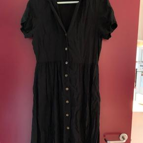 Den er svær at se på billedet, men det er en kjole med krave og så knappes den foran med fine knapper
