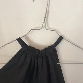 Sort silketop som bindes i nakken - fremstår som ny.