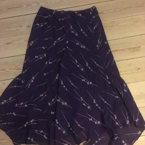 Fin lilla nederdel med lyselilla mønster og lille flæse for neden str. 42, men med elastik i taljen, så den kan passer større størrelser også.😀 Kan hentes i Århus midtby