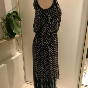 Feminin kjole i chiffon med hvide prikker fra Monsoon str 8/36. Fin detalje i ryggen. Integreret underkjole sikrer fint fald og at den ikke er gennemsigtig.