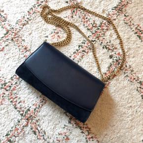 Fantastisk lækker og gennemført taske i mørkeblåt skind og ruskind. Skulderrem er guldfarvet og kan både bruges crossbody og dobbelt. Aldrig brugt. Dustbag og autenticitetskort medfølger.