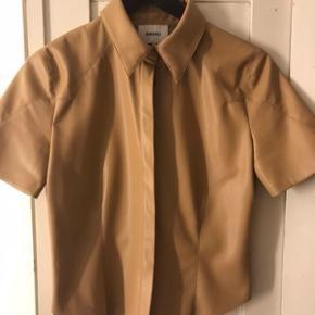 Slimfit skjorte i vegan leather.  Flot til højtaljet bukser eller nederdel.