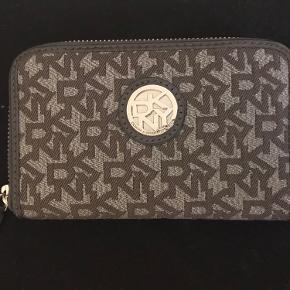 Fin grå/sølv pung fra DKNY. Pungen har en aflang form, en stor rum med lynlås til mønter og en del lommer til kort osv.   Pungen er brugt, men ser ny ud uden tegn på fejl eller slid.  Kan afhentes i Kbh SV eller sendes på købers regning.