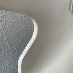 Den klassiske myre af Arne Jacobsen med de originale 3 ben produceret af Fritz Hansen.   Stolen er købt antikvarisk, hvor den er blevet nyrenoveret. Det kan kun ses bagpå, når man er helt tæt på, at der er lagt et lag maling ovenpå det originale.  Stolen kan sagtens bruges ved spisebordet, men der er begyndende små krakeleringer som vist på billederne.   Jeg har mest brugt stolen som pyntegenstand med coffee table books eller smukke blomster.  Spørg gerne for flere billeder, hvis det skulle være nødvendigt.   Prisen er sat efter standen.
