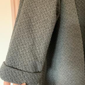 Lang cardigans med ærmer, der går ned over albuen. Farven grå og størrelse S, men lidt oversize, så mere en størrelse M.