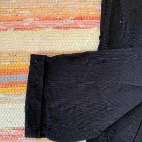 Sorte chinos. 100% bomuld, men med fløjlslignende look. Bindebånd foran og elastik bagtil i livet.   Fejler intet.