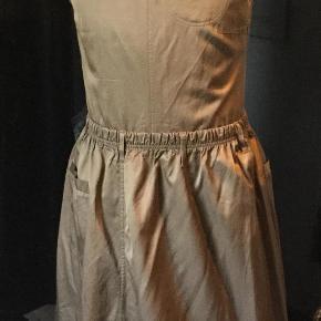 Materiale:60% bomuld, 40% viskose.  Stoffet er lidt blankt.  På det sidste billed ses hvordan den nederste del af kjolen vendes, så det ligner en nederdel med top.  Utrolig sød og anvendelig kjole med en sjov detalje. Farve: Brun