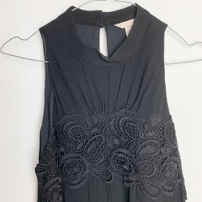 H&M sort broderikjole med blondekant nederst. Der står ikke hvad den er lavet af, men det er nok en form for bomuldsblanding.