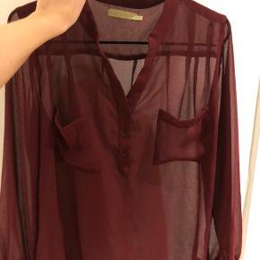 Transparent bordeaux skjorte med lommer og knapper. Str. S/M  Styles nemt med top under, hvis man ikke ønsker det transparente look.  Bud modtages.