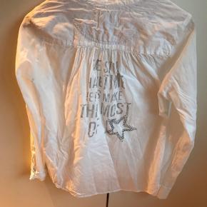 Så fin skjorte med simili stjerne og tekst på ryggen.. små dødningehoved knapper😉Kun brugt to gange..  Har den også i grå ( se annonce ) Tag begge for 150,-
