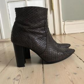 Varetype: Støvletter Farve: Brun Oprindelig købspris: 1499 kr.  Fede støvler i slangeskindslignende læder  I supergod stand, kun snuderne er lidt brugte, men det ses kun hvis man ligger på gulvet og kigger på dem:-)). Se foto  Sælges fordi jeg ikke længere kan gå i høje sko. De er 9 cm høje  Sender med dao