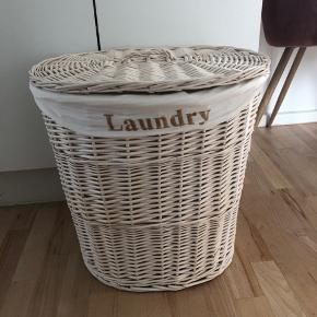 """Vasketøjskurv i lyst træflet """"Laundry"""" fra Jysk. Posen indvendigt kan vaskes, hvis det ønskes. Indersiden af låget bæger præg af brug men er fuldt funktionel. Kan afhentes i Kbh NV/ydre Nørrebro/Bispebjerg st."""