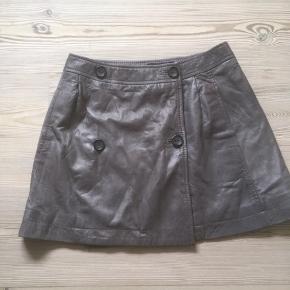 Mærke: Bruuns Bazar Størrelse: 36 Farve: Lysgråbrun  Materiale: 100% læder Nederdelen: Foret Nederdel fungerer som slå om på forsiden. Læderet er handske blødt. Skal sidde lidt nede  på hoften Længden:36 cm  taljemål: 70 cm  Kun brugt få gange  Sælges kr 350
