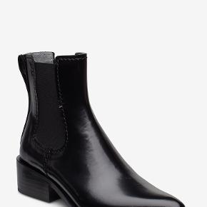 Skønne Chelsea støvler fra det svenske mærke Hope i shiny læder. Støvlerne er stylen 'West Chelsea', og kan stadig findes på Hope Stockholms hjemmeside, hvor de koster 3200 kr 🖤   Sælges lidt billigere, idet der er en lille afskrabning på indersiden af begge hæle (se sidste billede). Det kan måske pudses væk med farvet læderfedt.   Tags: støvler, vinterstøvler, læder, skindstøvler, Chelsea boots