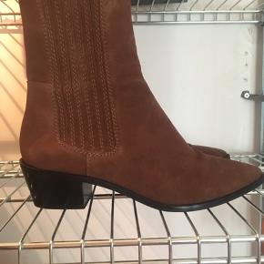 Brune/rust ruskindsstøvler med en lille hæl på ca. 2,5 cm.  Skaftet går til over anklen