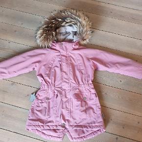 Lækker Vinterjakke str 116 Fra Mini a ture. Med flot ægte pels, jakken har et lille hul ved en af trykknapperne,Prisen er sat derefter. Se billedet.  Ellers i pæn stand.
