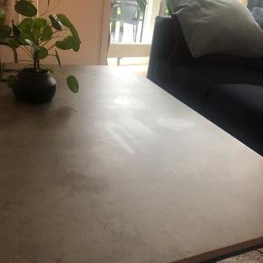 Dokkedal sofabord fra Jysk - nypris 599kr.  Kunstfiner betonlook og metal ben. B75 x L115 x H45 cm.  På billede to kan man se de mærker bordet har fået, efter varme glas/tallerkner etc.