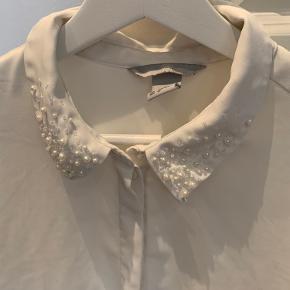 Fin skjorte med perler ved kraven og den øverste knappe er også en lille perle.