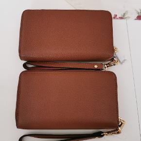 To smukke læderpunge fra Michael Kors med masser af plads til kort og plads til telefon.  Aldrig brugt, fremstår som nye.  Nypris 900,- stk.  Sælges for 350,- stk   Sendes på købers regning.