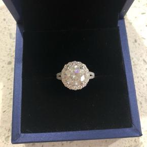 Produkt type: Moissanite diamant ring i 18k hvidguld. Total Moissanite vægt: 3,5 CTW Center Moissanite: 3ct ekvivalent (DEF VVS) Centersten størrelse: 9mm (i alt 13mm)  Guldvægt: 4g  Ring størrelse: S Certifikat på Diamanten fåes med.   Flot og elegant hvidguld ring, der kan bruges til en hver lejlighed eller som forlovelsesring.  Ringen har aldrig været brugt.   Normal pris: 15.000-20.000kr