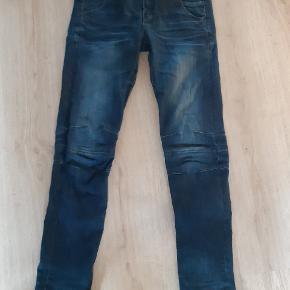 Fede jeans i str 28/32 med smalle ben og lynlås i ben. Fed detalje med skråskåret kant ved ankler. Lav talje og stræk. Brugt 2 gange og uden brugsspor.