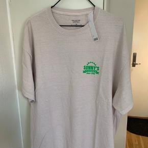 Lys sandfarvet / khaki / beige T-shirt fra UO med grønt Sunny tryk i str M 100% blød bomuld. Længde ca 72,5-73 cm Bredde fra ærmegab til ærmegab ca 58-58,5 cm (R stadig i butik til 299)