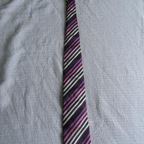 Sælger følgende stykke tøj, da jeg ikke får det brugt. Det er ejet af en ikke-ryger, fra et ikke-ryger hjem uden dyr. Slipset er i super god stand og stort set ikke brugt.  1. HUGO BOSS slips i silke. Farve: Sort / Lilla / Pink / Hvid. Perfekt til at fuldende det business-look, der sikre dig den forfremmelse hos Maersk.  Ny pris: 600 kr.   BETALING: Modtager kontanter, mobilepay (på nummeret i min brugerprofil) eller bankoverførsel.  AFHENTNING/FORSENDELSE: Kan afhentes på adresse/by angivet i denne annonce/min profil, eller tilsendes for købers regning.