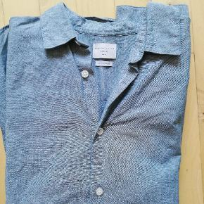 Skjorten er en støvet grøn, og i rigtig pæn stand, da den stortset er ubrugt