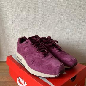 Sælger disse flotte Nike Air Max 1 i en flot Bordeaux ruskindsfarve.  Skoen er ubrugt. Kun brugt til billeder indendørs. Aldrig prøvet på. Kommer med original kasse.  Det indvendige mål er 30cm
