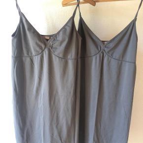 Sælger 2 stk. for 50 kr. + 35 kr. dao porto. Basic grå kjoler i 2 forskellige grå nuancer / lange toppe med V-udskæring fra Saint Tropez. Kvalitet microfiber: 95% Polyamide, 5% Elastane. Næsten som ny. Nypris 170 kr. pr. Stk. Kan stort set passes af alle fra s - xl, da stoffet er meget fleksibelt. Jeg rydder op og sælger ud.