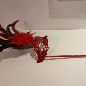 Super flot rød maske med dekorative sten, glimmer og fjer🎭 masken sidder på en fin pind med bånd, så den let og ubesværet kan tages til og fra ansigtet👌 en perfekt maske til en perfekt pris🤩