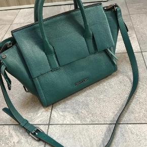 """Varetype: Crossbody Størrelse: Medium Farve: Grøn  Køber betaler fragt   Calvin Klein taske """"Cara bag"""" Brugt få gange Står som ny.  Dustbag medfølger. Nypris 3000,-"""