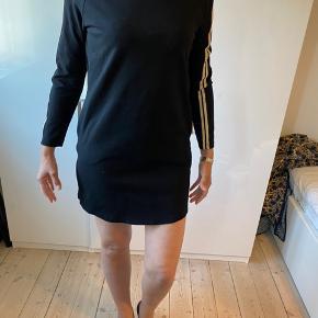 Sort  kjole med 'guld-bånd' ned af ærmerne. kraftigt, blødt og elastisk 'joggingtøjs-stof'  Aldrig brugt. Nål stadig i mærket men tag røget af.