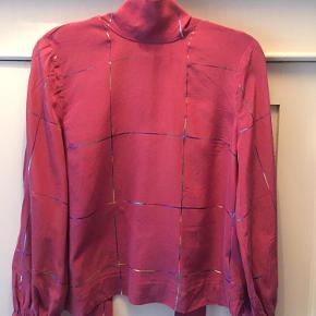 Smukkeste Goya-skjorte i silke med pussy bow, som bindes i nakken. Stoffet er pink med multifarvede glimmerstriber.