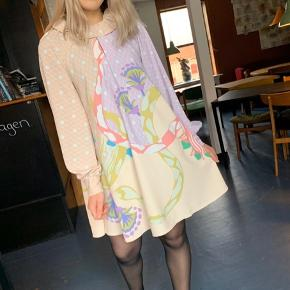Aldrig brugt!! Fuldstændig ny! Bytter ikke!! Prisen er fast!!!  Measurements for size small Chest 106 cm Bottom width 217 cm Sleeve length (from neckline) 76 cm Full length 89 cm   Vini Dress in Nile Pastel print with an oversized collar. This soft and flowy dress is cut above the knee with a voluminous A-line silhouette, long sleeves with buttoned cuffs and a loop neckline with a hook-and-bar closure.  The Nile print appears in two contrasting colourways representing day and night, both seamlessly blending mythological snakes, lotus flowers and papyrus reeds in a stylized painting typical of Egyptian art. Mixing soft hues of sand, lilac, yellow and emerald, this version of the print feels romantic and feminine. The Nile Pastel print appears on four styles.