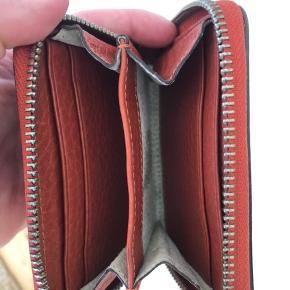 Rød/orange pung. Fejler ingenting, men har mindre brugsspor.