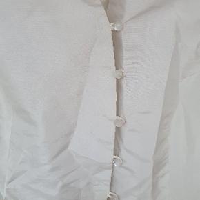 Fin hvid jakke i silkelook med unik skæv lukning af perleknapper. Er selv str. M og har brugt den lettere oversize.